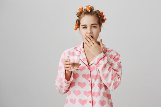 Senna Nastolatka W Lokówki I Piżamie Ziewanie, Trzymając Szklankę Wody Darmowe Zdjęcia