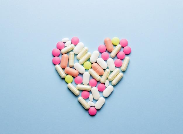 Serce Jest Ułożone Z Tabletek Na Niebieskim Stole. Zdrowie. Medycyna. Apteka. Premium Zdjęcia