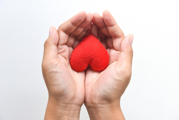 Serce pod ręką dla koncepcji filantropii. kobieta trzyma czerwone serce w ręce na walentynki lub przekazuje pomoc, aby dać ciepło miłości, dbaj Premium Zdjęcia