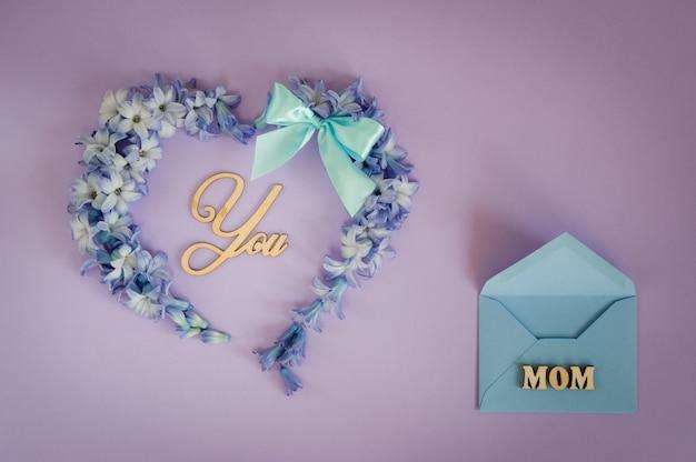 Serce robić od hiacyntowych kwiatów z nowym łękiem i drewnianymi listami na purpurowym tle. Premium Zdjęcia