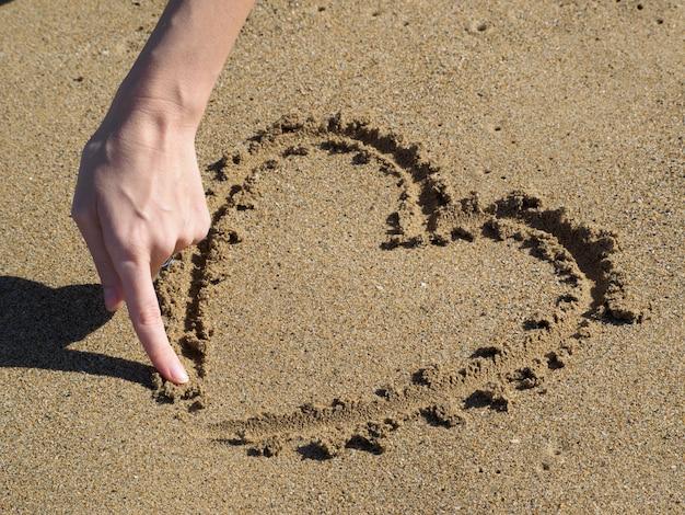 Serce Rysuje Palec W Piasku. Ręka Kobiety. Premium Zdjęcia