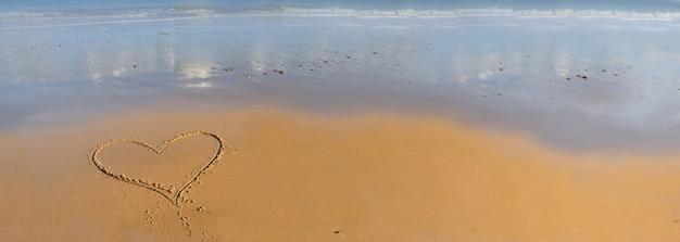 Serce rysunek na piasku nad brzegiem morza Premium Zdjęcia