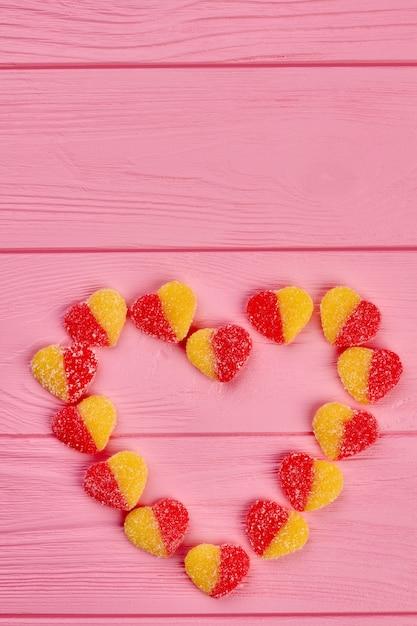 Serce Z Cukierków, Widok Z Góry. Kolorowe Cukierki Tworzące Kształt Serca Na Różowym Tle Drewnianych, Miejsce. Koncepcja Wakacje Walentynki. Premium Zdjęcia