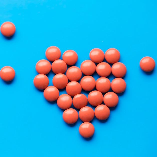 Serce Z Tabletów Na Niebieskim Tle. Pigułki Opieka Zdrowotna. Zatrzymaj Koronawirusa Premium Zdjęcia