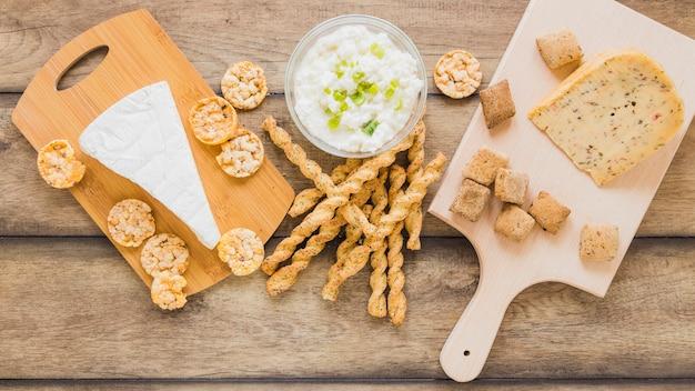 Serowe Ciasteczka I Paluszki Chlebowe Z Serem W Misce Na Drewniane Tła Darmowe Zdjęcia