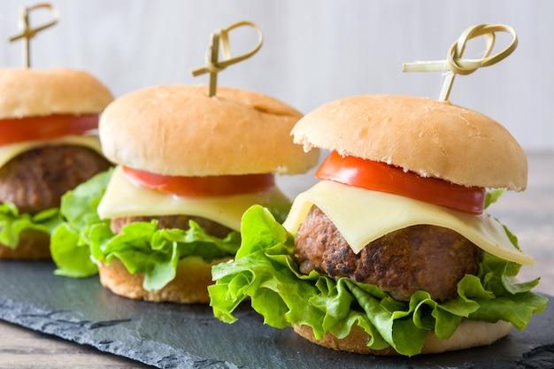 Serowy Hamburger Z Warzywami Na Drewnianym Stole Premium Zdjęcia