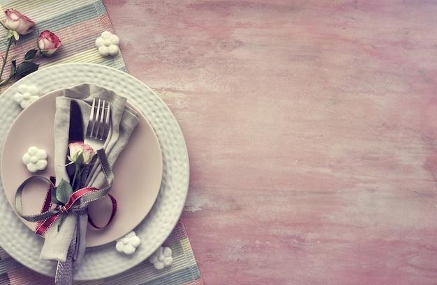 Serwetka I Naczynia, Ozdobione Różanym Pączkiem I Wstążkami, Wokół Ceramiczne Kwiaty I Różowe Róże Premium Zdjęcia