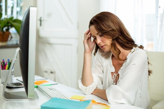 Sfrustowany Bizneswoman Relaksuje Przy Biurkiem Premium Zdjęcia