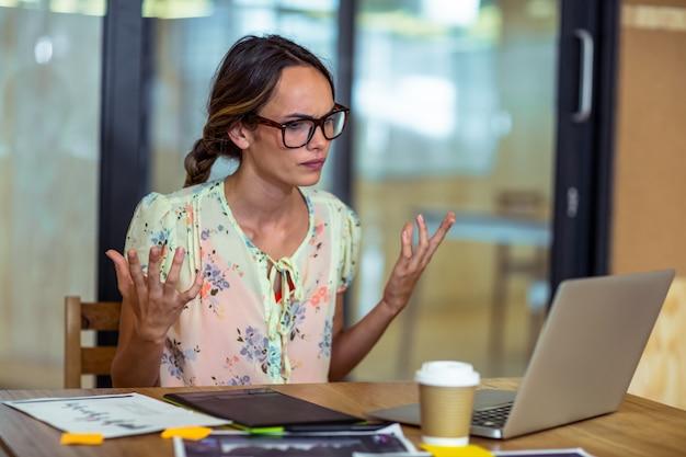 Sfrustowany żeński Projektant Graficzny Patrzeje Laptop Premium Zdjęcia