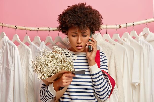 Sfrustrowana Młoda Kobieta Dzwoniąca Przez Smartfona, Zmartwiona Patrzy Na Kartę Kredytową, Trzyma Bukiet, Pozuje Przy Szafie Darmowe Zdjęcia