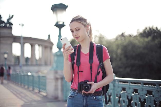 Shallow Focus Strzał Młodej Kobiety Robi Wycieczkę Po Mieście I Trzymając W Rękach Smartfon Darmowe Zdjęcia