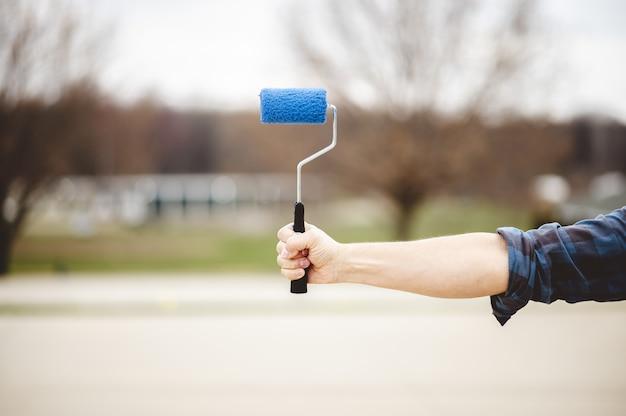 Shallow Focus Strzał Z Ręki Trzymającej Niebieski Pędzel Kufel, W Parku Darmowe Zdjęcia
