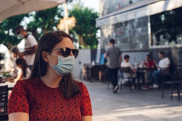 Shallow Fokus Strzał Kaukaski Kobieta Ubrana W Maskę Medyczną I Okulary Przeciwsłoneczne, Siedząc W Kawiarni Darmowe Zdjęcia