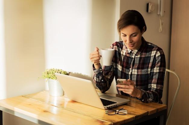 Shot Cute Młoda Kobieta Wiadomości Z Domowego Biura Podczas Filiżankę Kawy Premium Zdjęcia