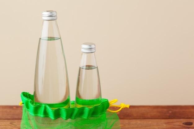 Siatkowe torby z szklaną butelką wody wielokrotnego użytku. Premium Zdjęcia