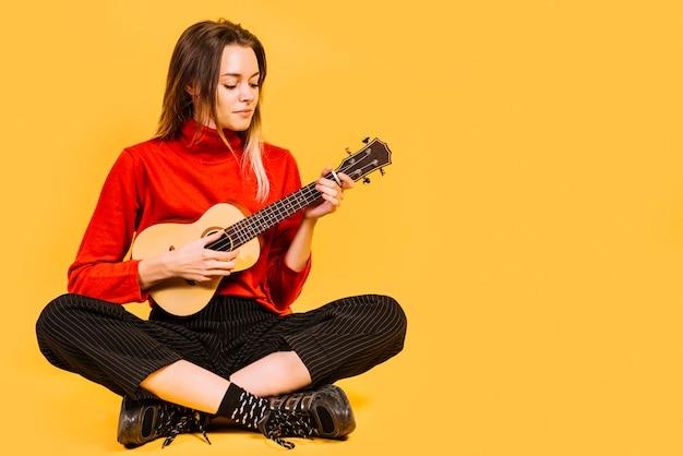 Siedząca dziewczyna gra na ukelele Darmowe Zdjęcia
