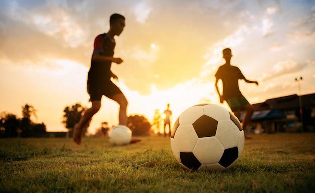 Silhouete sport akcji na zewnątrz grupy dzieci bawiących się w piłkę nożną Premium Zdjęcia