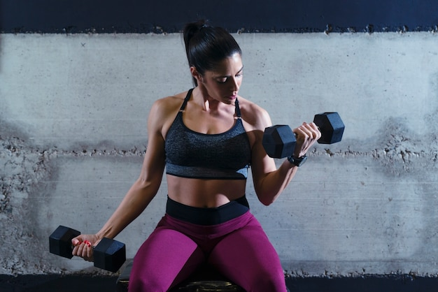 Silne Fitness Mięśni Kobieta Ciężko Pracuje Na Siłowni Podnosząc Ciężary I Bicepsy Treningowe Darmowe Zdjęcia