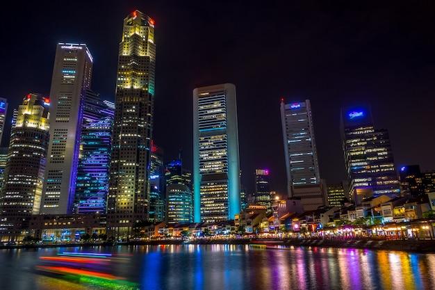 Singapur. Nabrzeże Z Kawiarniami I Wieżowcami. łodzie Wycieczkowe. Noc Premium Zdjęcia