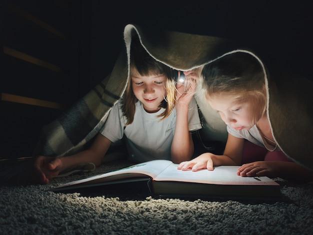 Siostry Czytające Książkę W Nocy Premium Zdjęcia