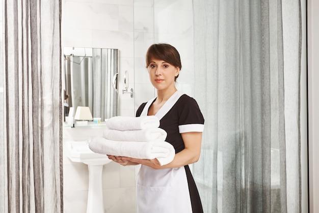 Sir, Położę Dodatkowe Ręczniki W łazience. Portret Kobieta W Gosposia Munduru Pozyci Z Białymi Hotelowymi Ręcznikami Blisko Drzwi Z Spokojnym I Poważnym Wyrażeniem, Jest Na Pracie W Hotelu Darmowe Zdjęcia