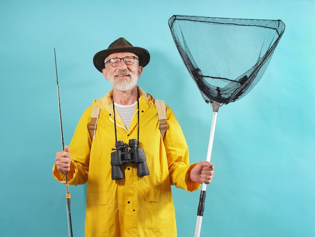 Siwowłosy Mężczyzna Z Brodą Ubrany W żółty Płaszcz Przeciwdeszczowy Trzyma Wędkę I Sieć Na Odosobnionym Tle Premium Zdjęcia