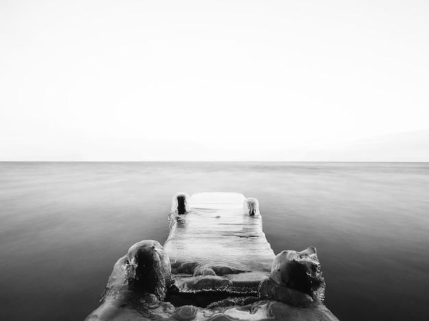 Skala Szarości Mostu Pokrytego Lodem Na Morzu Pod Słońcem Darmowe Zdjęcia