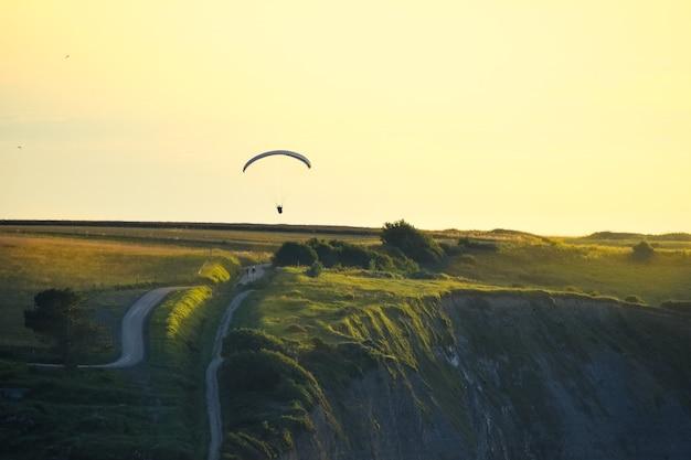 Skaliste Klify Pokryte Zieloną Trawą O Zachodzie Słońca. Mężczyzna ćwiczący Nad Nimi Paralotniarstwo. Premium Zdjęcia
