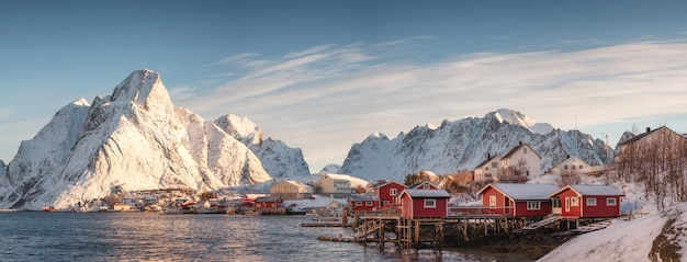 Skandynawska wioska z śnieżną górą przy linią brzegową w ranku Premium Zdjęcia