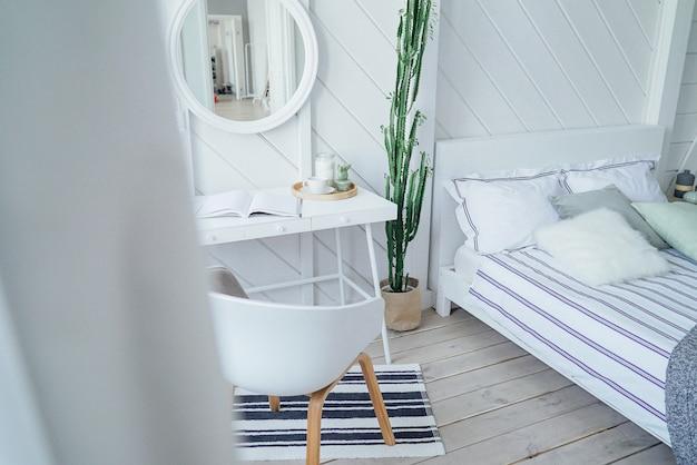 Skandynawski nowoczesny przytulny ekologiczne wnętrze, biały stół i lustro w sypialni Premium Zdjęcia