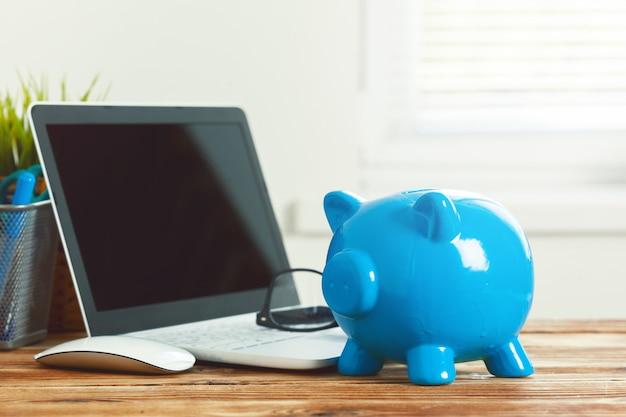 Skarbonka skarbonka z laptopa na drewnianym stole Premium Zdjęcia