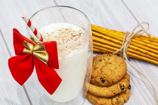 Skład z bożenarodzeniowymi ciastkami i mlekiem na białym tle Premium Zdjęcia