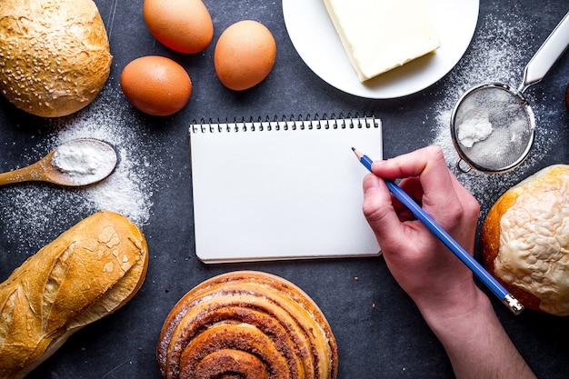 Składniki Do Wypieku Mąki I Produktów Piekarniczych żytnich. świeży Chleb, Bagietka, Bułki I Otwarta Książka Kucharska Na Czarnym Tle Tablicy Premium Zdjęcia