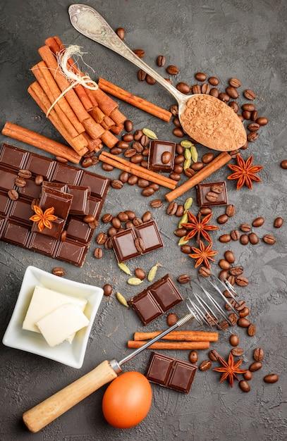 Składniki na desery - ciemna czekolada, kakao, kawa, cynamon, anyż, kardamon, przyprawy i przyprawy na czarnym tle, widok z góry Premium Zdjęcia