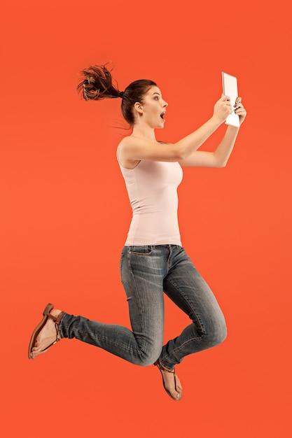 Skok Młodej Kobiety Na Niebiesko Przy Użyciu Gadżetu Laptopa Lub Tabletu Podczas Skakania. Uciekająca Dziewczyna W Ruchu Lub Ruchu Darmowe Zdjęcia