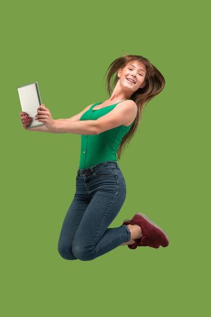 Skok Młodej Kobiety Na Zielono Przy Użyciu Gadżetu Laptopa Lub Tabletu Podczas Skakania. Uciekająca Dziewczyna W Ruchu Lub Ruchu Darmowe Zdjęcia