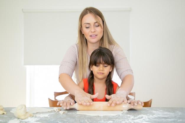 Skoncentrowana Dziewczyna I Jej Mama Toczenia Ciasta Na Kuchennym Stole Z Mąką W Proszku. Darmowe Zdjęcia