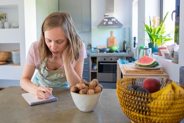 Skoncentrowana Gospodyni Domowa Planuje Tygodniowe Menu W Swojej Kuchni, Zapisuje Listę Zakupów W Notatniku. Gotowanie W Domu Koncepcja Darmowe Zdjęcia