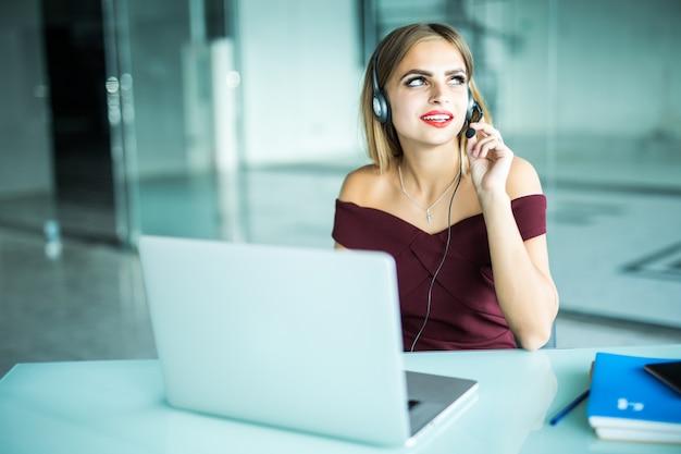 Skoncentrowana, Uważna Kobieta W Słuchawkach Siedzi Przy Biurku Z Laptopem, Patrzy Na Ekran, Robi Notatki, Uczy Się Języka Obcego W Internecie, Kurs Online Samokształcenie W Sieci Konsultacje Z Klientem Przez Wideo Darmowe Zdjęcia