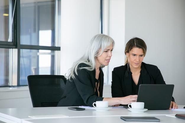Skoncentrowane Panie Biznesu Oglądając Treści Na Laptopie Siedząc Przy Stole Z Filiżankami Kawy I Rozmawiając. Koncepcja Pracy Zespołowej I Komunikacji Darmowe Zdjęcia