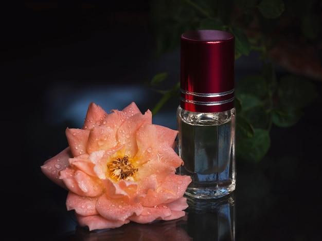 Skoncentrowane Perfumy W Mini Buteleczce Z Różową Pachnącą Herbatą Na Czarnym Tle Premium Zdjęcia