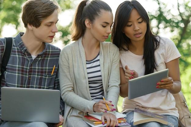 Skoncentrowani Uczniowie Siedzący I Studiujący Na Zewnątrz Darmowe Zdjęcia