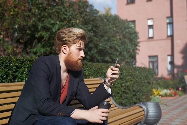 Skoncentrowany Brodaty Hipster Za Pomocą Smartfona, Siedząc Na ławce Darmowe Zdjęcia