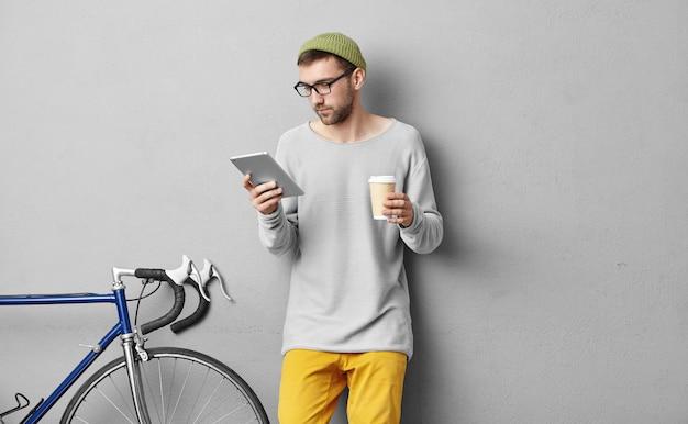 Skoncentrowany Mężczyzna W Modnych Dużych Okularach, W Jednej Ręce Trzymający Tablet, W Drugiej Kawa Na Wynos, Wybierający Się Na Rowerową Wycieczkę W Góry, Czytający W Internecie, Co Lepiej Zabrać Ze Sobą Darmowe Zdjęcia