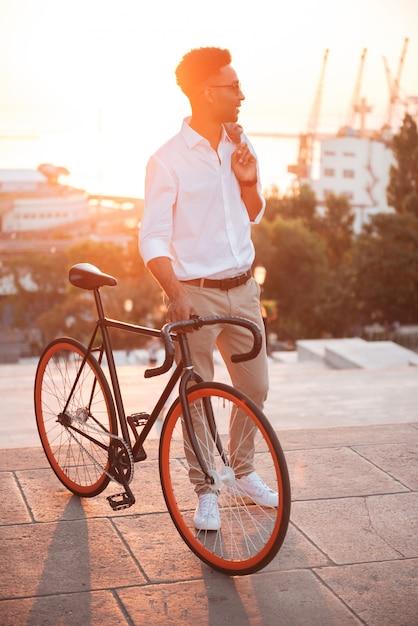 Skoncentrowany Młody Afrykański Mężczyzna W Wczesnym Poranku Z Bicyklem Darmowe Zdjęcia