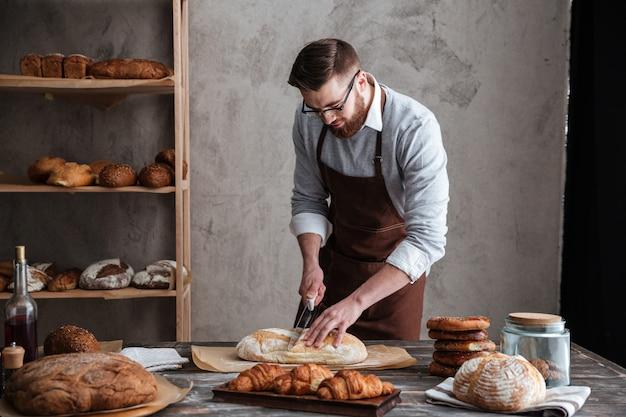 Skoncentrowany Młody Piekarz Pokroił Chleb. Darmowe Zdjęcia