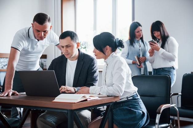 Skoncentrowany Na Pracy. Ludzie Biznesu I Menedżer Pracujący Nad Nowym Projektem W Klasie Darmowe Zdjęcia