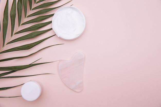 Skrobak Do Gwaszu Z Różowego Kwarcu Na Różowym Tle. Zabieg Przeciwstarzeniowy, Liftingujący I Tonizujący W Domu. Premium Zdjęcia