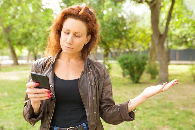 Skupiająca Się Poważna Kobieta Z Smartphone Czytelniczą Wiadomością Darmowe Zdjęcia