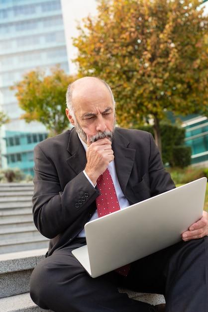 Skupiający Się Dojrzały Biznesmen Używa Laptop Outdoors Darmowe Zdjęcia